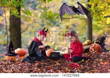 Two funny kids wearing devil and vampire costume with red horns and trident trick or treating on Halloween. Children dressed up as witch play in autumn park.