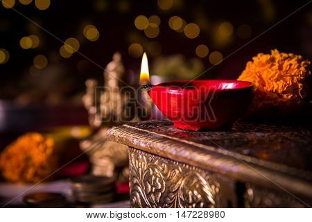 oil lamp or diya with crackers, sweet or mithai, dry fruits, indian currency notes, marigold flower and statue of Goddess Laxmi on diwali night