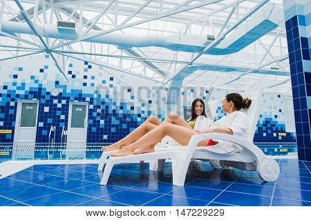 Two beautiful women are lying on chaise-longue poolside indoors and talking