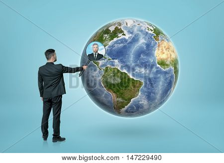 Back view of a businessman looking through magnifying glass on the Earth and seeing a portrait of a man. Global communication. International business. Elements of this image are furnished by NASA