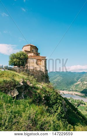 Mtskheta, Georgia. The Ancient Georgian Orthodox Church Of Holly Cross, Jvari Monastery With Remains Of Stone Wall, World Heritage. Scenic Blue Cloudy Sky Background.