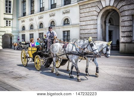 VIENNA AUSTRIA - JUNE 24 2016: People have a ride in the fiaker and pass the Hofburg in Vienna. The fiaker first was build in the 18 century in the street Rue de Saint Fiacre.