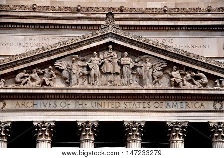 Washington DC - April 11. 2014: The classical facade and ornate tympanum allegorical bas reliefs of the 1837 Archives of the United States building on Constitution Avenue
