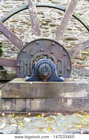 Axle of old water wheel with spokes projecting from it.