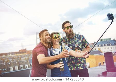 Three happy friends with selfie stick taking a picture of themselves while drinking beers on top of roof in city