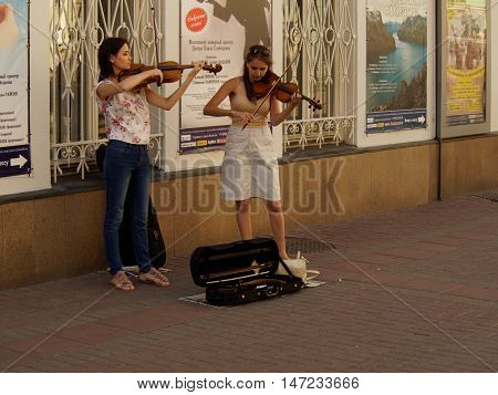 MOSCOW, RUSSIA - August 28, 2016: Two young women students playing violins on the walking street Arbat.. August 28, 2016 in Moscow, Russia