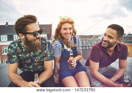 Two men and a woman drinking beer while sitting on roof in city with bright sunny sky behind them