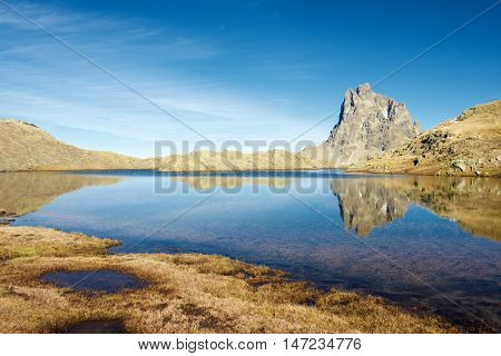 Midi Dossau Peak reflected in a lake. Ossau Valley, Pyrenees National Park, Pyrenees, France.