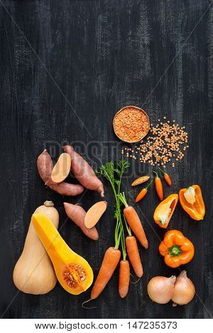 Raw organic produce vegetables for butternut soup, orange coloured food on dark background