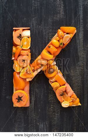 Flat lay series of healthy orange produce fruit and vegetables shaped into letters of alphabet, design element poster spelling layout
