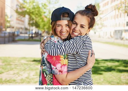 Two happy pretty young female friends with vivacious smiles hugging each other in a close embrace in a quiet urban setting
