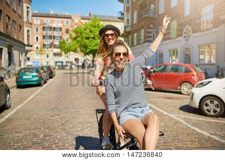 Grinning pretty young woman waving at the camera as she rides on the handlebars of a friends bicycle down a cobbled urban street