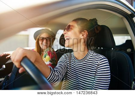 Smiling happy young woman giving her friend a lift in her car in town profile view through the open side window with sun flare
