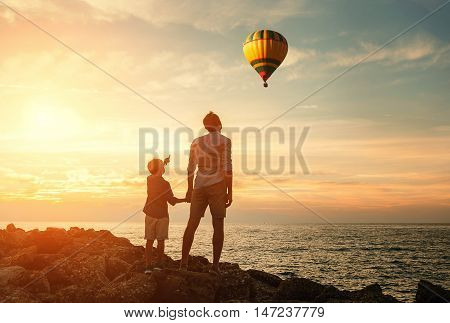 Father with son look on the balloon on the sea coast