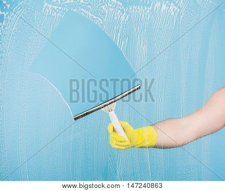 Cleaning conept - hand cleaning glass window pane with detergent and rubber wiper