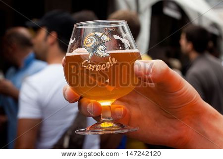BELGIUM, BRUSSELS - SEPTEMBER 07, 2014: Belgian Beer Weekend 2014. The most famous beer festival in Belgium. Glass of Caracole beer at the festival.