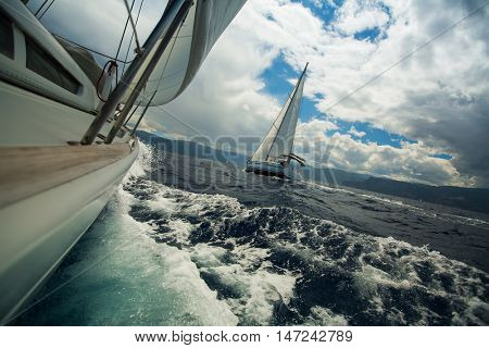 Sailing ship luxury yachts during a race regatta in the Sea at stormy weather.