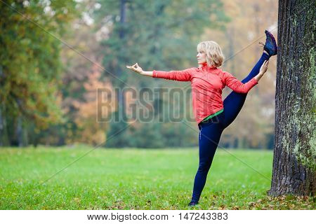 Young smiling happy woman doing yoga in autumn park. Caucasian blonde girl exercising and training yoga stretching outside in nature. Sport fitness and exercising motivation and inspiration.