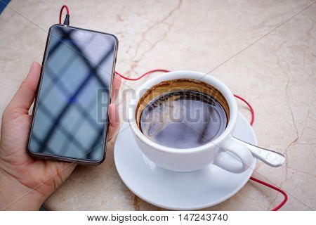 Smartphone at hand and americano coffee in white cup at marble table top