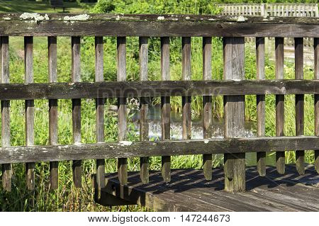 A well worn and weathered wooden fence still standing and doing its job.