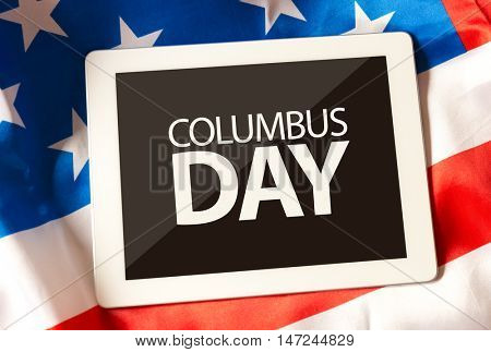 Columbus Day on tablet and the US flag