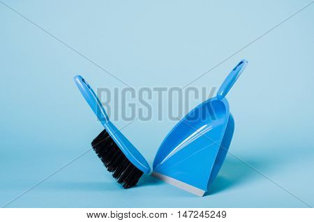 Cleaning concept - dustpan and sweeper on blue gradient backdrop