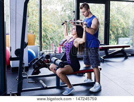 Young athletic woman doing pull down exercise for the back under a personal trainer's supervision