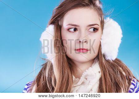 Teenage girl wearing fluffy white earmuff in winter fashion cold time.