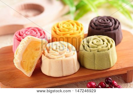 Colorful mooncake on a wooden tray with one half-cut
