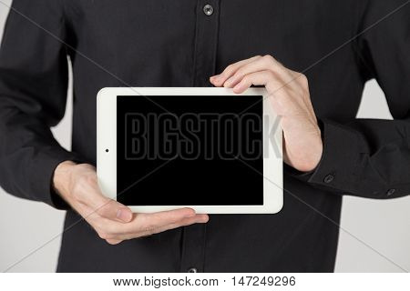 Business man holding and shows touch screen tablet pc with blank screen