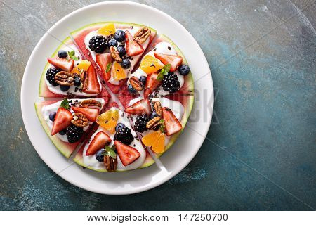Watermelon pizza with fruits, yogurt and berries, coconut flakes and cocoa nibs