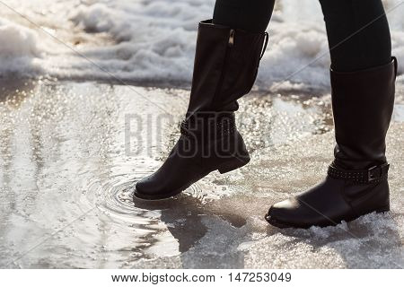 girls legs in boots trying to go on puddle at snow.