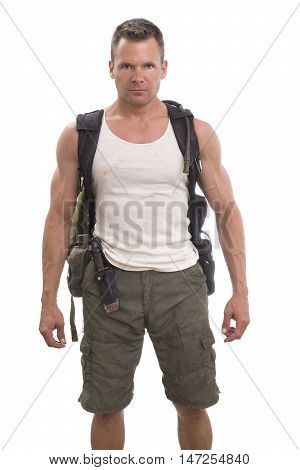 Handsome muscular man with hiking and expedition gear wearing cargo shorts and tank top standing on white background with bold action figure expression