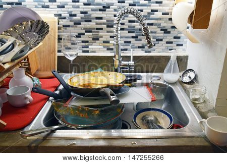 Dirty sink filled with dishes in a messy household kitchen