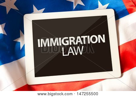 Immigration Law on tablet and the US flag