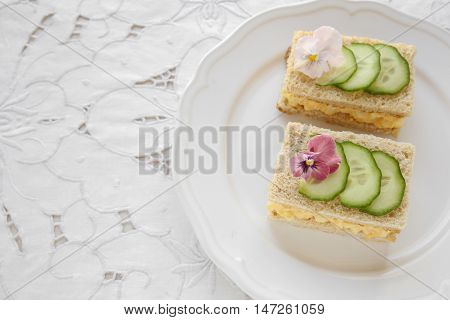 Egg And Cucumber Afternoon Tea Sandwiches With Edible Flowers, Copy Space Lace Background