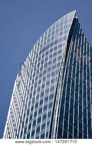 Vancouver, BC - April 20, 2015 - beautifully shaped glass and steel office building in the middle downtown Vancouver on a beautiful sunny day with a bright blue sky reflecting on it windows. Shot at a slightly skewed perspective to further enhance it's sp