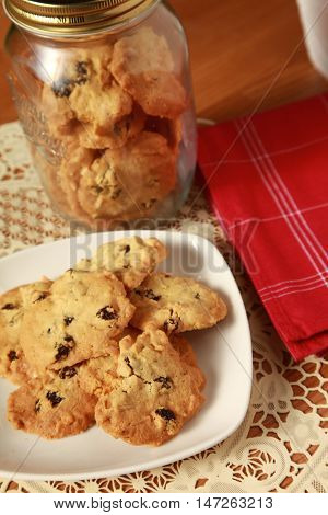 Raisin cookies served in wooden table with jar