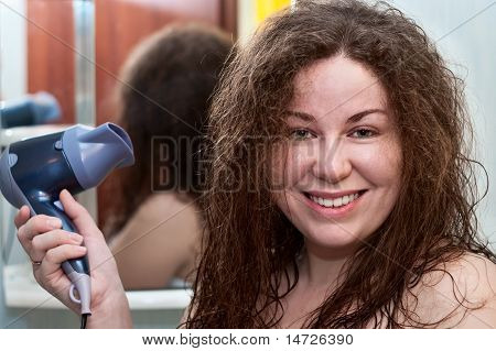 Young Caucasian Woman With Curly Brown Bushy Hair Holding Hairdryer