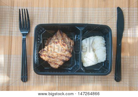 grilled pork with sticky rice in box on mat