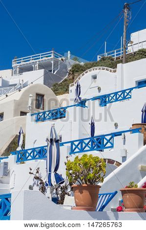 Greek house with terrace on the hill. Flower pot on foreground. White architecture on Santorini island Greece