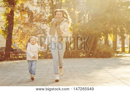 Family walk. Mother and daughter running through the autumn park. Healthy lifestyle. Autumn Park.