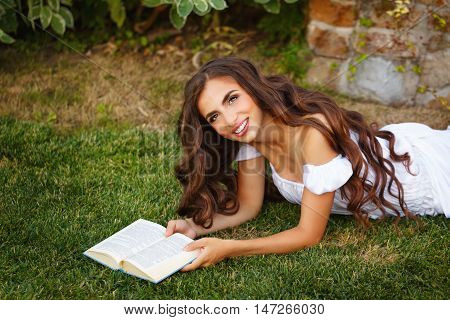 Lovely girl reading a book lying on a green lawn. Romantic and poetic girl with long hair.