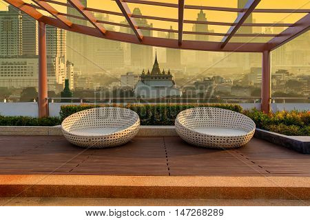 Relax corner on condominium rooftop garden with chairs on landmark bangkok Golden Mount Temple in the sunrise time background Landmark concept