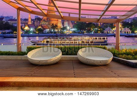 Relax corner on condominium rooftop garden with chairs on landmark bangkok Wat Arun and cruise ship in night background Landmark concept