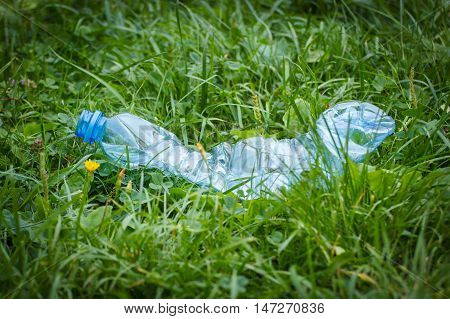 Plastic Bottle Of Mineral Water On Grass In Park, Littering Of Environment