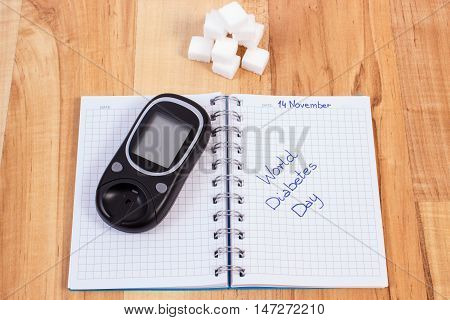 Glucometer, World Diabetes Day Written In Notebook And Sugar Cubes