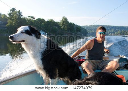 Man steers fishing boat through the waters of Lake of Bays as his dog stands up sniffing the breeze
