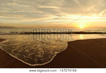 Sunset ocean is a bright sun setting on the ocean horizon as a gentle wave comes to shore.