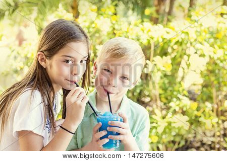 Cute kids sharing a delicious flavored ice drink together